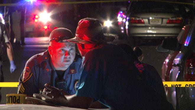 A Long Banch police officer speaks with a witness on Coleman Avenue in Long Branch late Wednesday evening, July 22, 2015, where a multiple shooting alledgedly occurred.