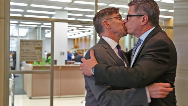 "Rob MacPherson, left, and Steven Stolen, who are married, say goodbye to each other after visiting Marion County Clerk Beth White to thank her for her support, at the Marion County Clerk's office in the City/County building, Monday, October 6, 2014.  The U.S. Supreme Court denied requests to take up the same-sex marriage issue, meaning gay marriage is legal in Indiana. MacPherson and Stolen were plaintiffs in the ACLU case, ""So we won today,"" they said."