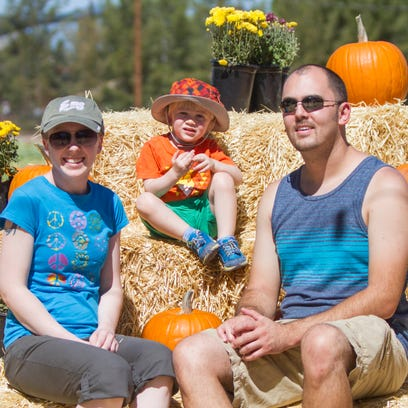 Malia and Ryan Ebner, of Avondale, sit with their son, Harvy, 2, next to pumpkins during the Schnepf Farms 2014 Pumpkin and Chili Party, Sunday, October 5, 2014, in Queen Creek, Ariz.