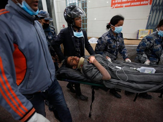 Survivor Rishi Khanal, 27, is carried on a stretcher after being freed by French rescuers from the ruins of a three-story hotel in the Gangabu area of Kathmandu, Nepal, Tuesday, following Saturday's earthquake.