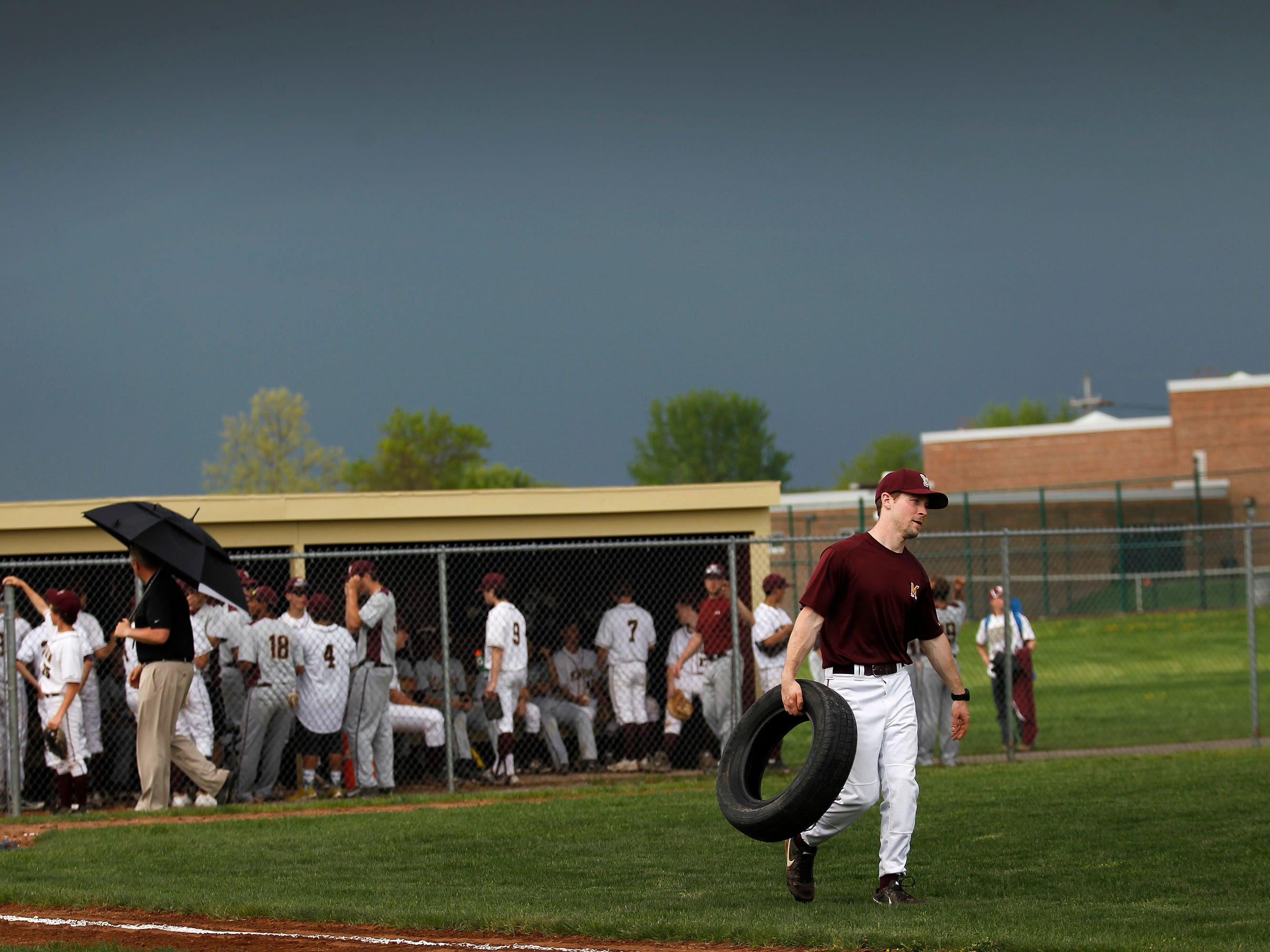 Members of the Pittsford Mendon baseball team start to cover home plate and the bases as the skies darken around them. The game was called after a thirty minute storm delay.