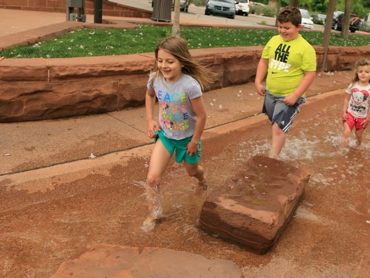 Peyton Larsen, 7, and her siblings Hudson, 8, and Paisley, 4, play in the creek Thursday at St. George Town Square while on vacation from Kaysville.