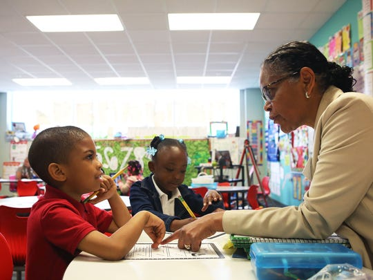 Shirley Bengework, a teaching assistant and retired teacher, works with Chad Gough and Mareona Long, during reading groups at George and Veronica Phalen Leadership Academy in Indianapolis Thursday, May 13, 2015. Phalen's school year is longer at 200 days, compared to the traditional school year at 180 days.