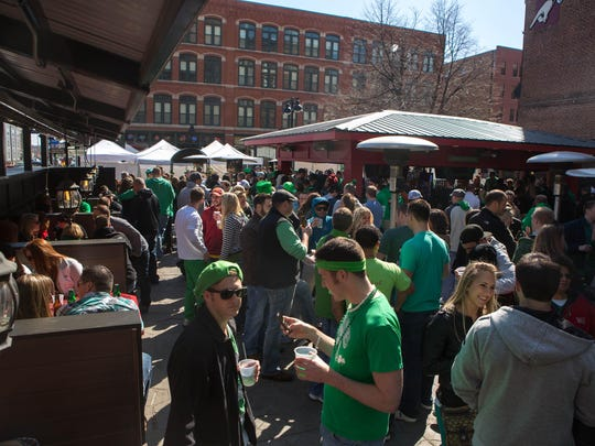 Visitors hang out during a St. Patrick's Day party at Mickey's Irish Pub in downtown Des Moines.