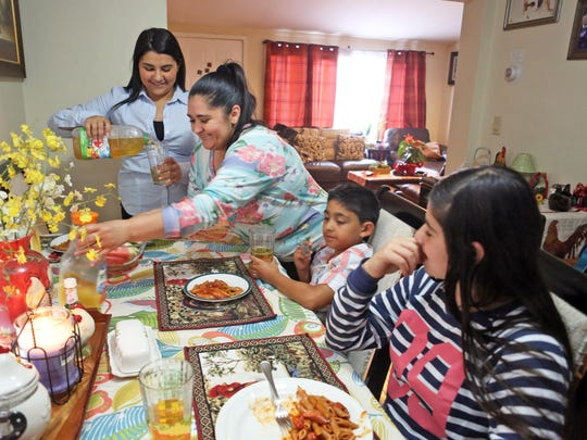 Lisdy Contreras-Giron, a senior at Fox Lane High School, helps her mother Edna Contreras get dinner on the table for her siblings Freddy Jr., 6 and Maddy, 12, at their home in Mount Kisco. Lisdy will be attending Pace University in the Fall.