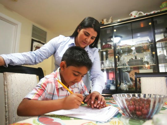 Lisdy Contreras-Giron, a senior at Fox Lane High School, helps her brother Freddy, Jr., 6, with his homework at their home in Mount Kisco. Lisdy will be attending Pace University in the Fall.