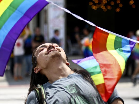 A man does a limbo dance under a string of rainbow colored flags set up in celebration of the Supreme Court's decision legalizing gay marriage across the United States, on Friday, June 26, in Atlanta. The high court's decision set off a wave of similar reactions nationwide and several same-sex marriages were officiated shortly after the ruling was issued.