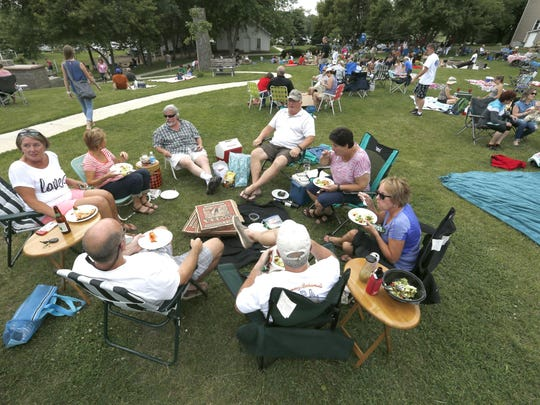In this June 24, 2015 photo, people gather at the Red Barn Farm near Northfield, Minn., to relax and enjoy pizza. Pizza farms, particularly popular in Minnesota and Wisconsin, provide small farms with extra income and city dwellers with opportunities to get in touch with their food sources.