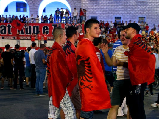 Albanian soccer fans shrouded in national flags as they gather at Mother Teresa Square in central Tirana to celebrate the three points awarded to Albania over Serbia by the top sports court, Tirana, Friday, July 10, 2015.  Reversing a UEFA sanction over a soccer game that was abandoned in Belgrade, Serbia, when a drone with an Albanian political banner flew into the stadium and sparked violence in October last year, Albania is now level on 10 points with second-place Denmark in Group I, and Serbia is now last on minus two points. (AP Photo/Hektor Pustina)
