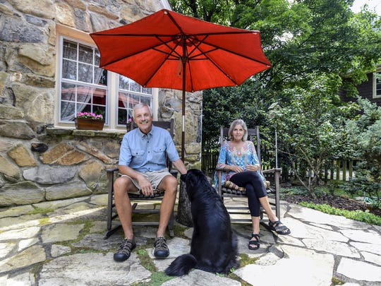 Mike Burgette and Jill Perkins sit outside their North Asheville home with dog Libby.