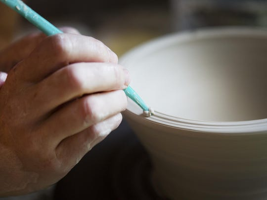 Jessie Marianacci Valone uses a tool to add texture to the rim of a bowl.