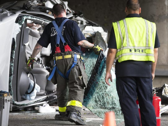 A Rochester firefighter carries a shattered windshield at the scene of a car accident on Route 104 at Portland Avenue on Friday.