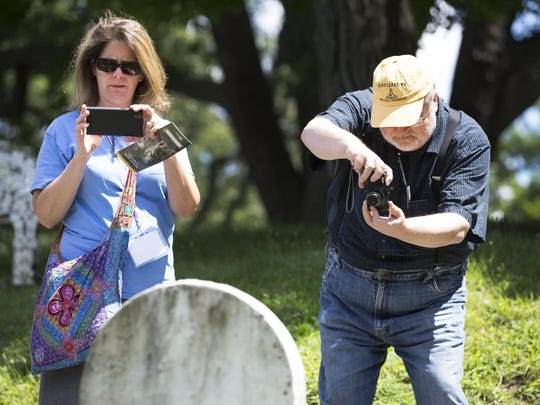Cari Reeves of Greensboro, North Carolina, and Michael Allard of Gainesville, North Carolina, photograph the grave of Susan B. Anthony while on a Rochester's reform history tour in Mt. Hope Cemetery on July 22, 2015.