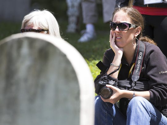 Cara Lane, an 11th grade American Literature teacher in Edwardsville, Illinois, listens to a tour guide speak about Susan B. Anthony at her grave in Mt. Hope Cemetery.