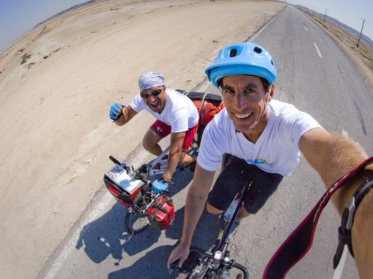 Rick Gunn and Mohammad Tajeran ride a road across the center of Qeshm Island Iran, in February of 2014.
