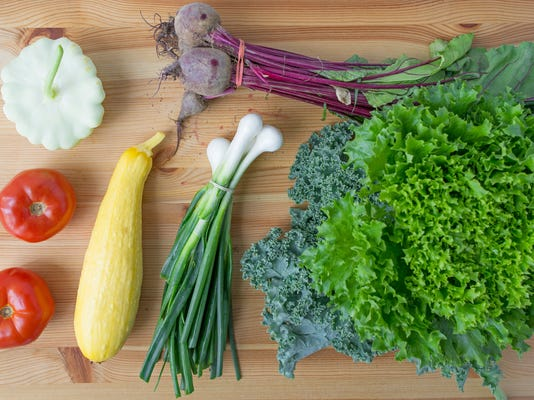 Clockwise, from top left: A white squash, beets, lettuce and kale, spring onions, yellow squash and tomatoes. Photo by Jeff Lautenberger.