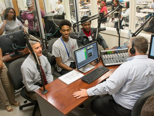 Superintendent Don Aguillard, left, and students Tyler Jolivette Byron Zeno talk with Jay Redmond, director of Northside's broadcasting and journalism academy, during the station's first live broadcast.