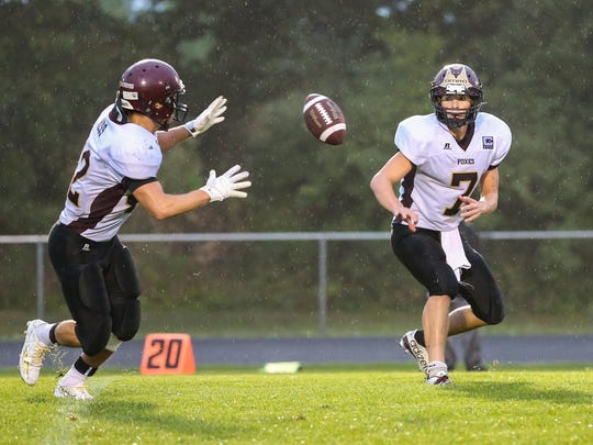 Omro's Spencer Potratz (7) pitches the ball to Chris Hess (42) in the first quarter of last week's game against Winneconne.