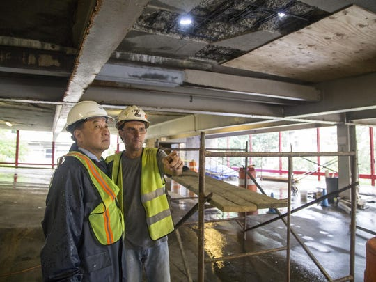 Sun-Hee Hwang, left, a senior engineer with architectural design firm Tim Haahs, and project supervisor Zoltan Ember inspect the Collier Street parking garage in July.