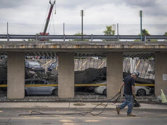 A worker walks past the collapsed parking garage at