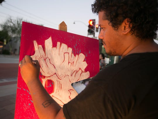 Once-empty downtown Mesa sidewalks are coming alive with revitalized businesses and special events. Aaron Motley of Mesa paints on the side of the street during a recent art walk.