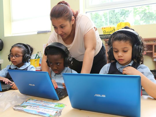 Teacher Jayden Estevez helps students working with laptops at the Charter School of Educational Excellence in Yonkers.