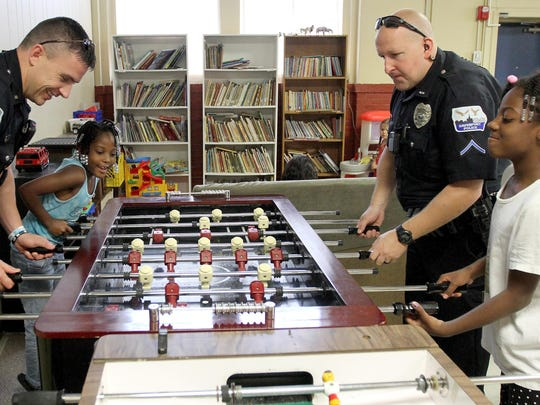 Davenport Police Cpl. Barry Peiffer, right, and Chanel Sims, left, play foosball with officer Jarrad Cockshoot, left, and Karyn Brown, right, in a game of fossball during a a weekly cookout at Lydia House in Davenport. It's part of the outreach efforts of the Davenport Police Neighborhoods Energized to Succeed, or NETS, unit.