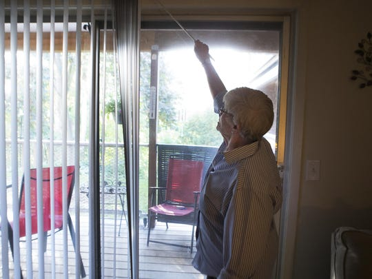 Beverly Lynn opens the blinds in the apartment she shares with her husband, John Morgan, at Penfield Skyline Apartments.