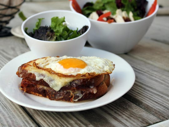 The croque madam is ham and cheese sandwich with Bechamel sauce, Swiss cheese and a sunny-side-up fried egg).