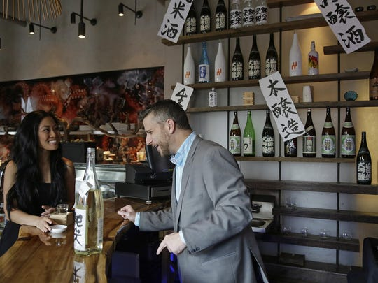 Lena Draiman, left, of Austin, Texas, learns about sake from sommelier Christian Lee while visiting the sake lounge at Morimoto Napa in Napa, California. The restaurant from Masaharu Morimoto, of Iron Chef fame, recently added the valley's first sake lounge.