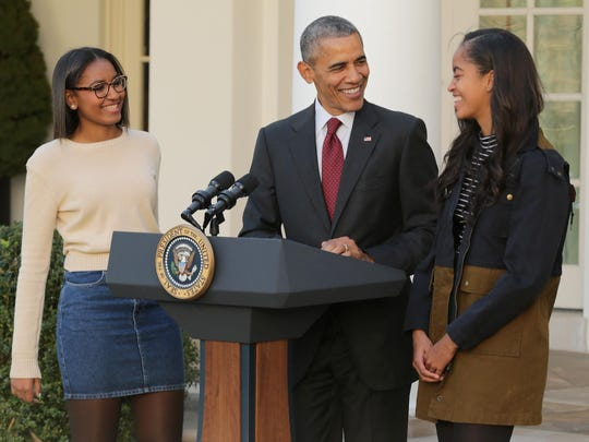 President Barack Obama delivers remarks with his daughters Sasha, left, and Malia during the annual turkey pardoning ceremony in the Rose Garden at the White House on Wednesday.