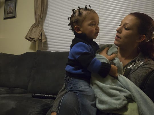 Recovering opiate addict Amber Townsend tries to comfort one of her five sons, Zhi'mareon, 1, at their home in Des Moines on Nov. 10. Amber, who has been sober for nearly a year, participates in a methadone program through United Community Services Inc.