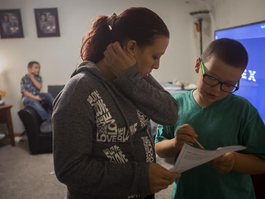 Recovering opiate addict Amber Townsend tries to help her son Mason, 10, with his homework at their home in Des Moines, Tuesday, Nov. 10, 2015. Amber, who has been sober for nearly a year, participates in a methadone program through United Community Services Inc. in Des Moines.