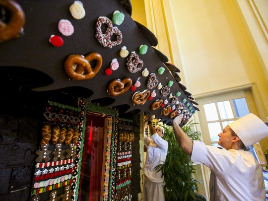 Emily Fredricks, pastry cook, sticks a pretzel to eave of the gingerbread home as she helps decorate it. The pastry chefs at The Ritz-Carlton in Naples are building a 13-foot-by-13-foot gingerbread house inside the lobby of the hotel Saturday, November 28, 2015. This is a six-month project that includes nearly 2,000 gingerbread shingles; 120,000 pieces of candy; and royal icing made with 44 pounds of egg whites and 391 pounds of icing sugar. By 3pm Saturday they were closing in on finishing the house.