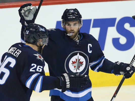 FILE - In this Wednesday, Dec. 2, 2015 file photo, Winnipeg Jets' Andrew Ladd (16) and Blake Wheeler (26) celebrate Ladd's goal against the Toronto Maple Leafs during third period NHL action in Winnipeg, Manitoba. The Chicago Blackhawks acquire Ladd in a trade with the Jets. (John Woods/The Canadian Press via AP, File)