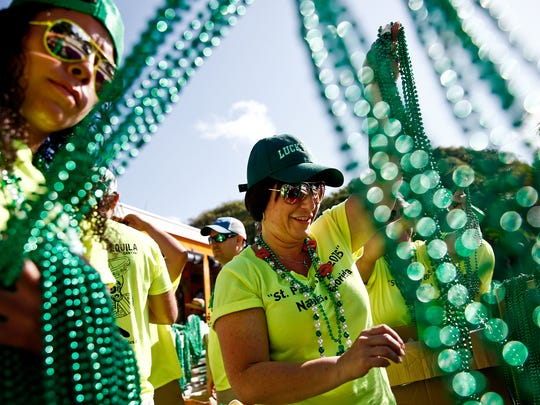 In this 2015 file photo, Gail Pauser, center, and Nicole Aviles sort beads that will be thrown to the crowd during the 39th Annual Naples St. Patrick's Day Parade through Downtown Naples on Saturday, March 14, 2015. Scott McIntyre/File