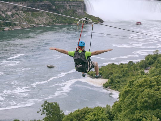 A tourist suspended above the water from zip lines makes his way at speeds of up to 40 mph toward the the mist of the Horseshoe Falls, on the Ontario side of Niagara Falls. The overhead cables have evolved from a fun way to explore jungle canopies to trendy additions for long-established outdoor destinations.