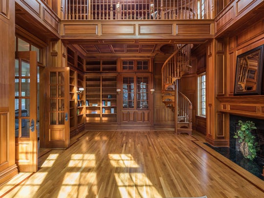 The library includes a secret door and a winding staircase up to a reading nook.