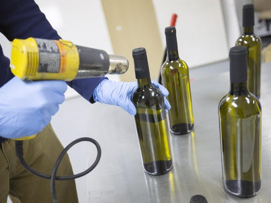 Kaelan Castetter uses a heat gun to seal bottles of his hemp-infused wine at the Sovereign Vines facility in Johnson City, Broome County.