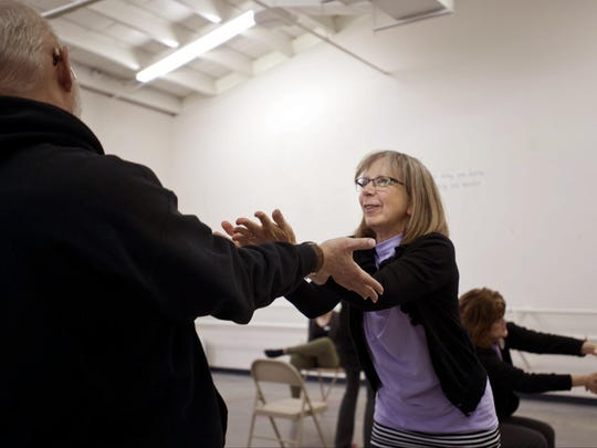 """Jan White points her hands towards her husband Roger White during a mimicking activity to the song """"What A Wonderful World"""" at Spotlight Dance Academy in Grand Haven, Mich."""