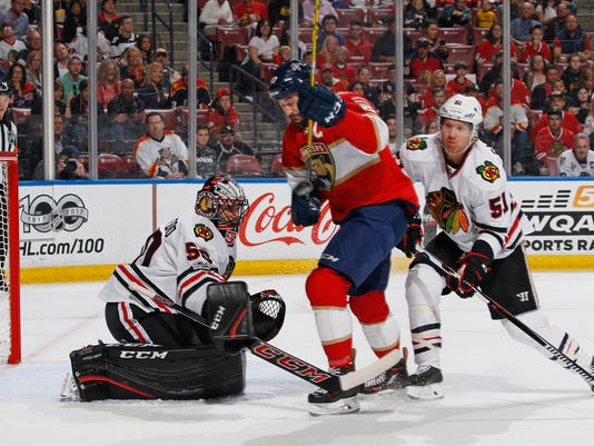 Chicago Blackhawks goaltender Corey Crawford (50) stops a shot by Florida Panthers center Derek MacKenzie (17) as he is checked from behind by Chicago Blackhawks defenseman Brian Campbell (51) during the first period of an NHL hockey game, Saturday, March 25, 2017, in Sunrise, Fla. (AP Photo/Joel Auerbach)