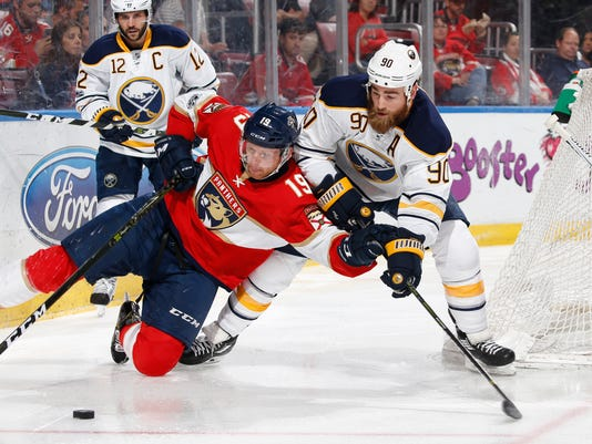 Florida Panthers defenseman Michael Matheson (19) falls to the ice as he attempts to keep the puck away from Buffalo Sabres center Ryan O'Reilly (90) during the second period of an NHL hockey game, Saturday, April 8, 2017, in Sunrise, Fla. (AP Photo/Joel Auerbach)