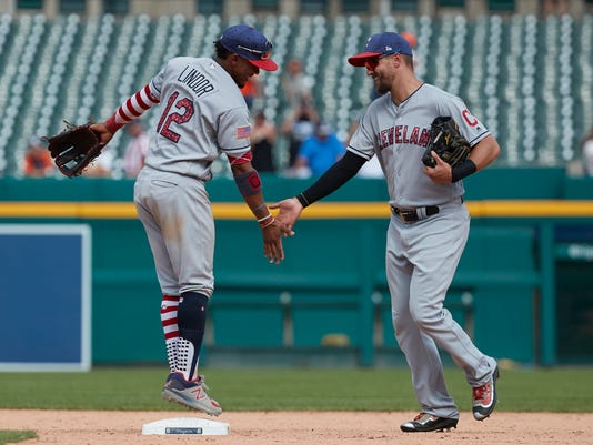 Cleveland Indians Francisco Lindor, left, Lonnie Chisenhall, right, celebrate after a baseball game against the Detroit Tigers in Detroit, Sunday, July 2, 2017. Cleveland won 11- 8. (AP Photo/Rick Osentoski)
