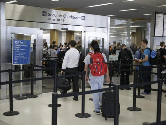 In this Wednesday, June 29, 2016, photo, a pair of travelers, at left, walk through a TSA Precheck security line, while other passengers wait in line to be screened, in Terminal 2 of San Francisco International Airport in San Francisco. Passengers at all U.S. airports will soon face new measures for screening electronic devices bigger than a cellphone. Security officers will ask travelers in regular lanes to take all larger devices out of their bag and put them in a bin by themselves, similar to the screening of most travelers' laptops. Officials say it gives X-ray screeners a clearer picture of the devices. The change won't apply to Precheck lanes. (AP Photo/Eric Risberg)