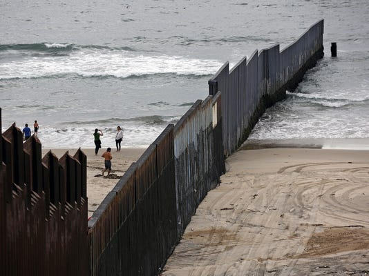 Where border fence meets the sea, a strange beach scene contrasting the US and Mexico