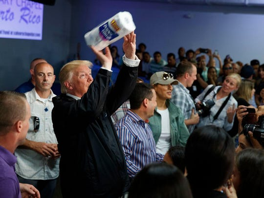 President Donald Trump tosses paper towels into a crowd as he hands out supplies at Calvary Chapel in Guaynabo, Puerto Rico, on Tuesday. Trump was in Puerto Rico to survey hurricane damage.