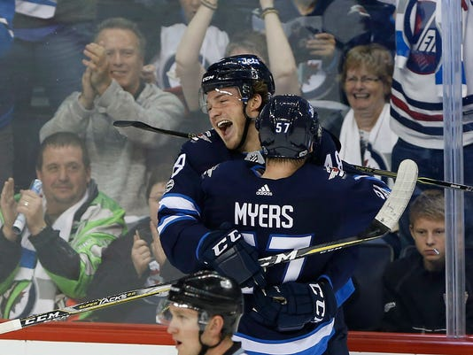 Winnipeg Jets left wing Brendan Lemieux (48) and defenseman Tyler Myers (57) celebrate Lemieux's first NHL goal against the Pittsburgh Penguins during the third period of an NHL hockey game in Winnipeg, Manitoba, Sunday, Oct. 29, 2017. (John Woods/The Canadian Press via AP)