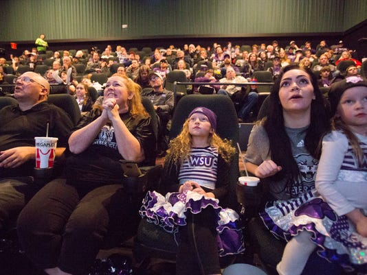 Rex Baxter, Jenn Baxter, Izzy Baxter, 9, Alexx Baxter, and Nyxx Baxter, 5, from left, alongside family and fans react after a play while watching television coverage of Weber State playing James Madison in the quarterfinals of the FCS NCAA college football playoffs, Friday, Dec. 8, 2017, in Ogden, Utah. (Matt Herp/Standard-Examiner via AP)