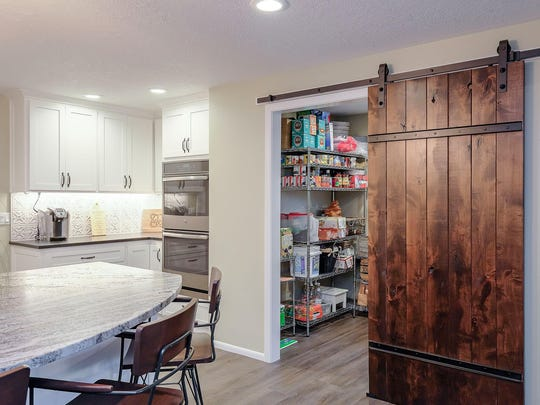 This Keizer home took advantage of a new large pantry customized to the owner's liking with portable shelving units bought at a home store. The sliding barnwood door makes a bold statement.