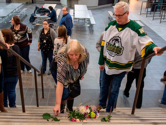 Humboldt mayor Rob Muench, right, in the Broncos team jersey, along with other mourners lay down flower on the stairs that enter to Elgar Petersen Arena, home of the Humboldt Broncos, in Humboldt, Saskatchewan, Canada on Saturday, April 7, 2018.  Canadian police said early Saturday that several people were killed and others injured after a truck collided with a bus carrying the junior hockey team to a playoff game in Western Canada. Police say there were 28 people, including the driver, on board the bus of the Humboldt Broncos team when the crash occurred around 5 p.m. Friday on Highway 35 in Saskatchewan.   (Liam Richards/The Canadian Press via AP)